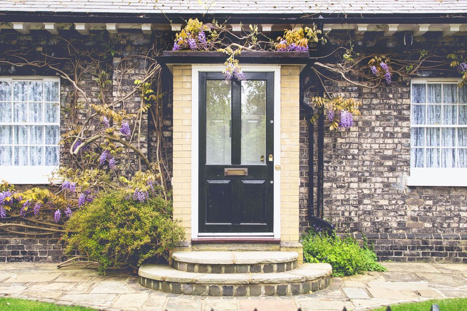 photograph of front door to a home with wysteria vines and purple flowers in front of brick facade