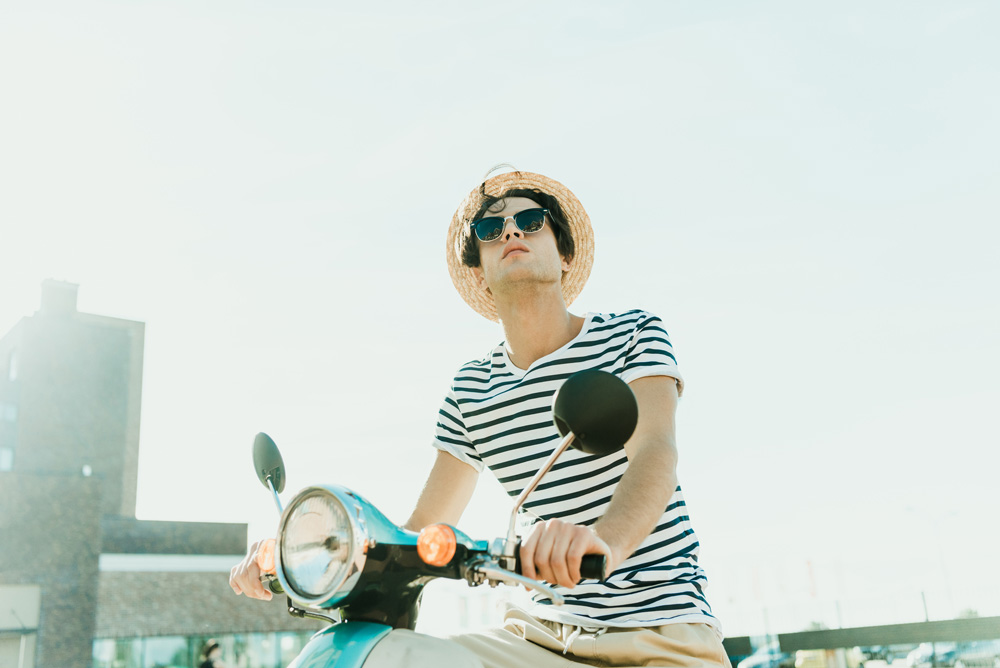 Millennial on scooter wearing hat and sunglasses looking up towards the blue sky