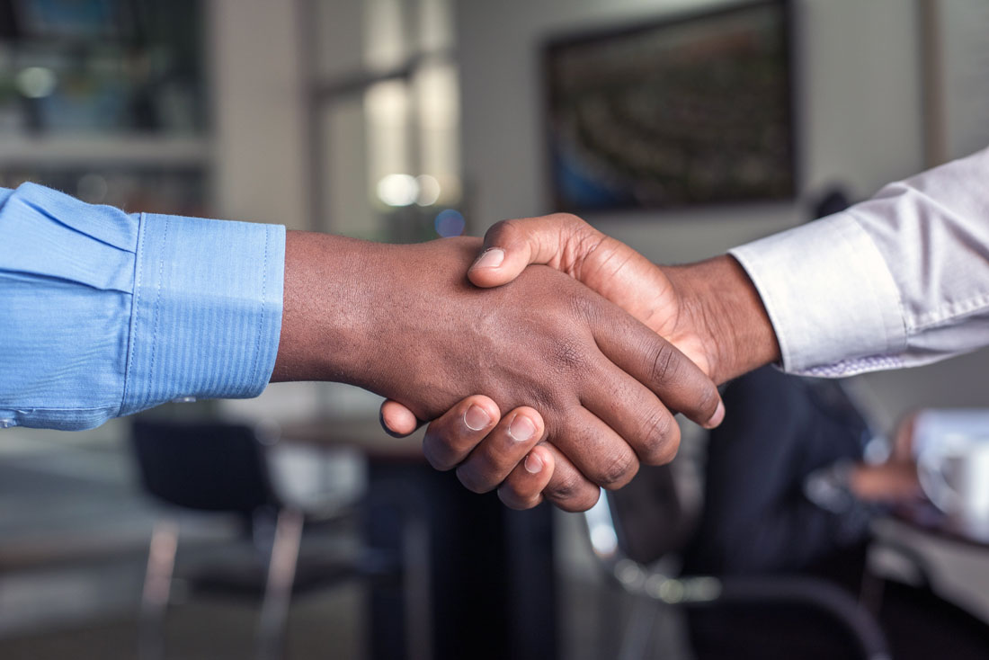 Two hands in a handshake, symbolizing agreement, congratulations, or relational warmth.